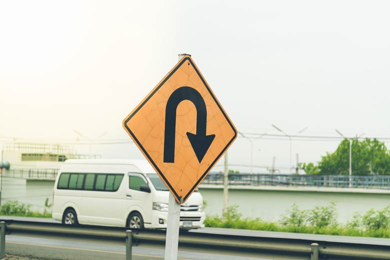 Gelb-orangenes U-Turn Schild auf einem Highway