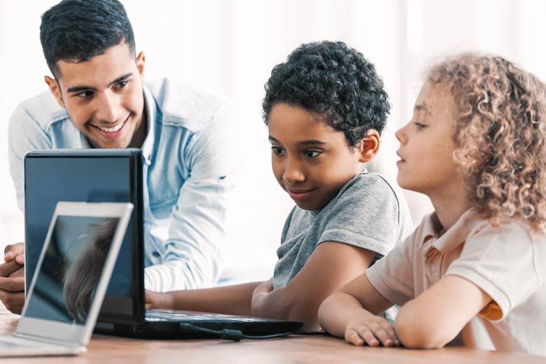IT Lehrer zeigt zwei Shülern die Basics im Programmieren