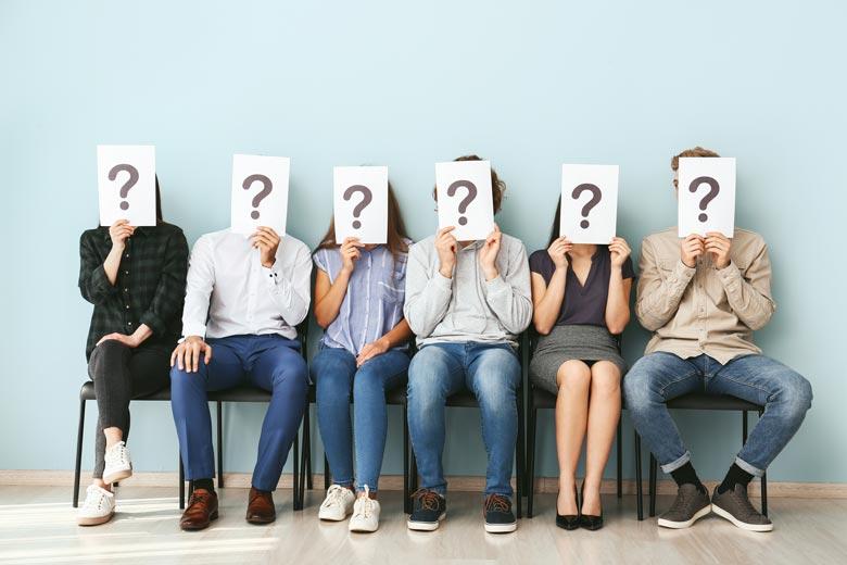 Junge Bewerber mit einem Fragezeichen vor dem Gesicht sitzen in einer Reihe und warten auf ihr Vorstellungsgespräch