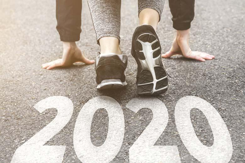 Junge Mitarbeiterin in Startposition auf der Zahl 2020