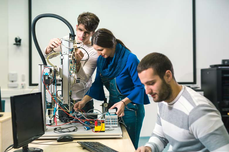 Junge Ingenieure und IT-Experten bauen eine pneumatische Schaltanlage