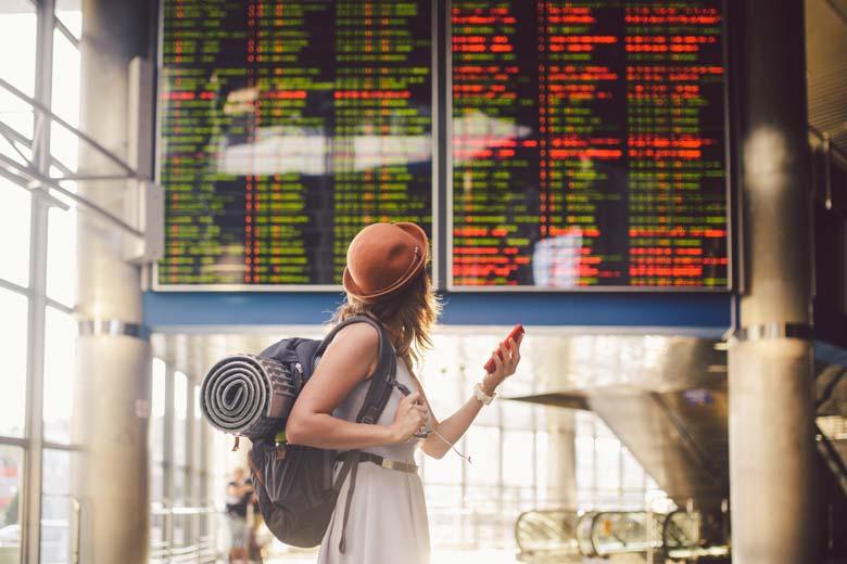 Junge Studentin auf reisen steht vor einer rießigen Anzeigentafel in einer Bahnhofshalle