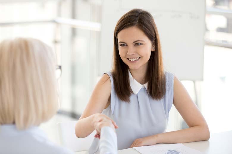 Lächelnde Frau gibt Personalerin im Vorstellungsgespräch die Hand