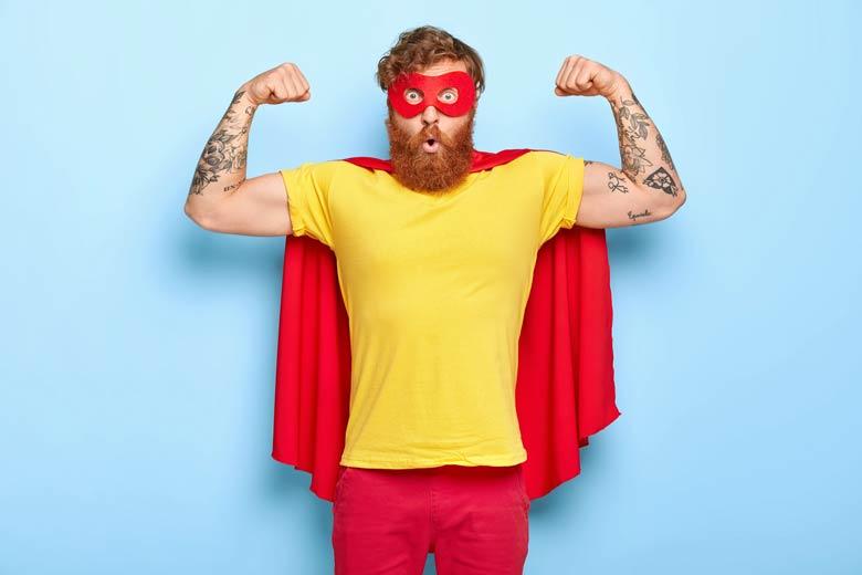 Rotbärtiger, tätowierter Bewerber als Superheld verkleidet