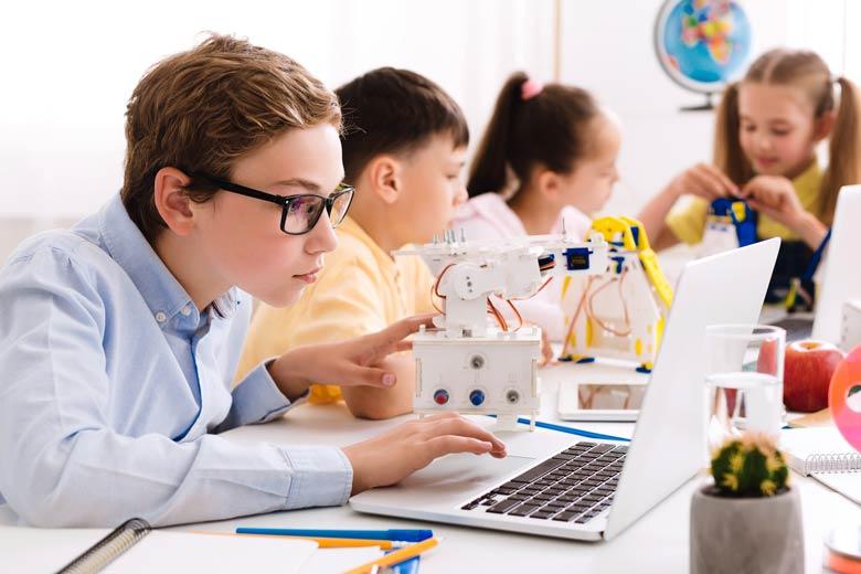 Technikaffine Kinder der Generation Alpha programmieren einen Roboter