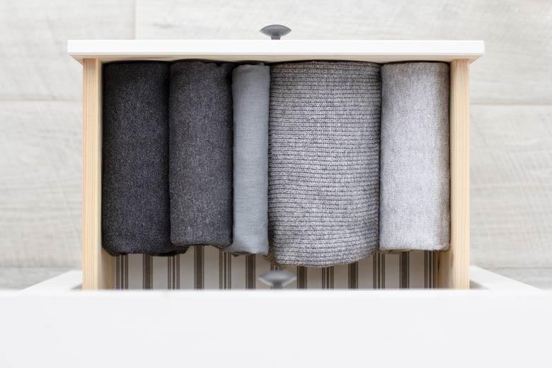 Vogelperspektive auf die geöffnete Schublade einer weißen Kommode mit grauen und schwarzen Schals darin
