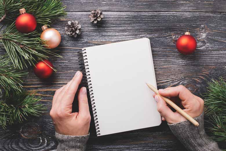 Zwei Hände über schreiben Notizen auf eine To-Do-Liste umringt von Weihnachtsdeko