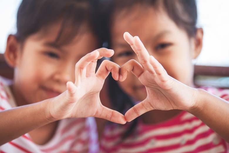 Zwei Kinder formen gemeinsam ein Herz mit ihren Händen