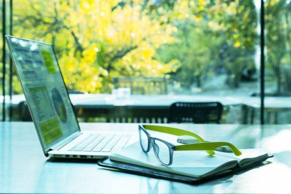 Aufgeklappter Laptop in einem Cafe mit Aussicht ins Grüne