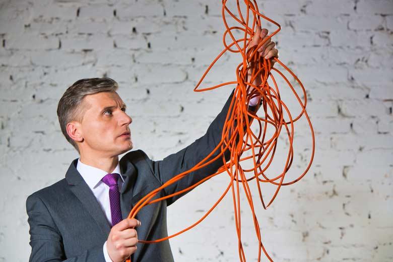 Geschäftsmann hält ein orangenes Kabel in die Luft und versucht es zu entwirren
