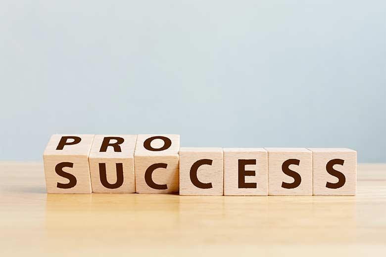 Hölzerne Würfel auf denen Process bzw. Success geschrieben steht