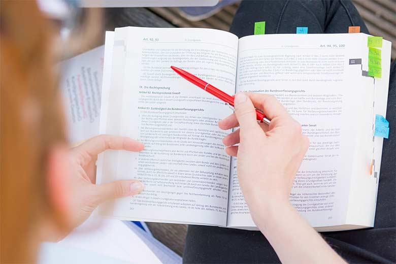 Jura Student liest gerade in einem Gesetzbuch