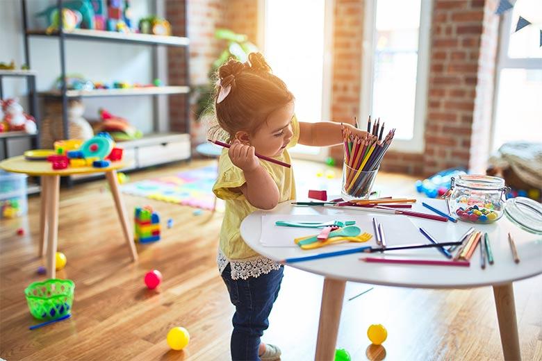 Ein kleines Mädchen lernt spielerisch in einem Spielzimmer