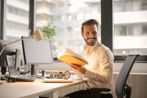 Lächelnder Mann an aeinem Arbeitsplatz im Büro