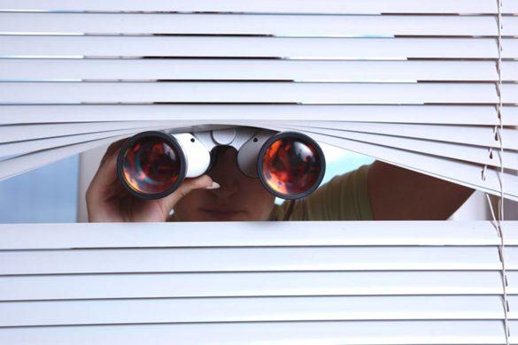 Neugieriger Typ schaut mit einem Fernglas durch eine Jalousie