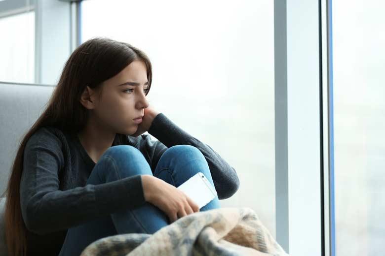 Trauriges Mädchen mit Smartphone denkt an ihren digitalen Nachlass