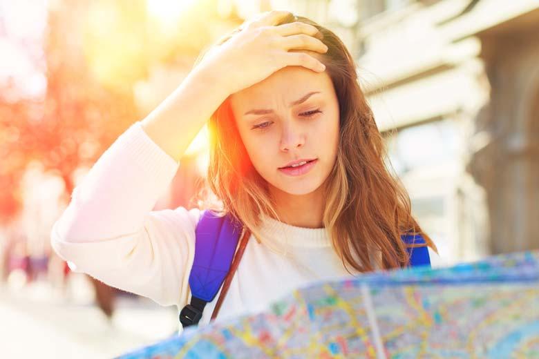Junge Absolventin schaut orientierungslos in eine Straßenkarte auf der Suche nach dem Weg zum High Potential