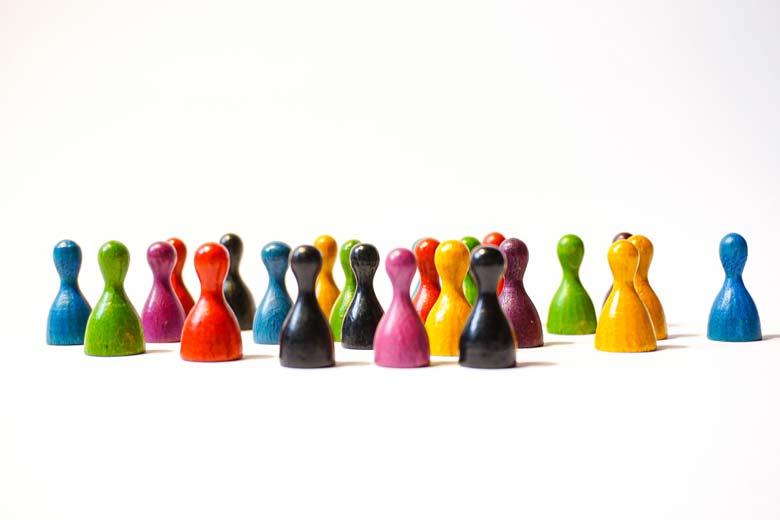 Spielfiguren in verschiedenen Farben stehen vor einem weißen Hintergund