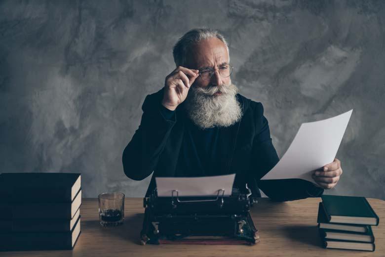 Älterer Mann schreibt seinen Lebenslauf auf einer Schreibmaschine
