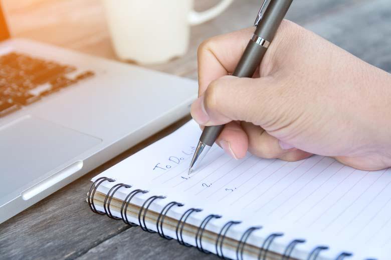 Eine Hand schreibt eine To-Do-Liste auf einen Block