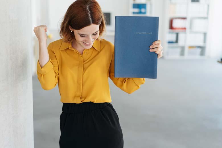 Junge Frau freut sich mit Bewerbungsunterlagen in der Hand