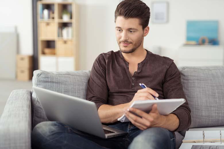 Junger Bewerber mit Laptop und Unterlagen schreibt gerade eine Initiativbewerbung