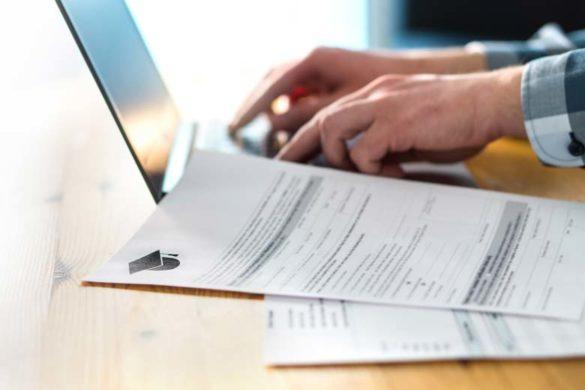 Laptop und Bewerbungsformulare auf einem Schreibtisch