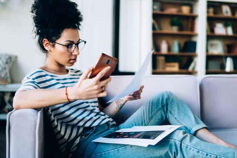 Studentin lässt sich von ihrem Smartphone vom Lernen ablenken