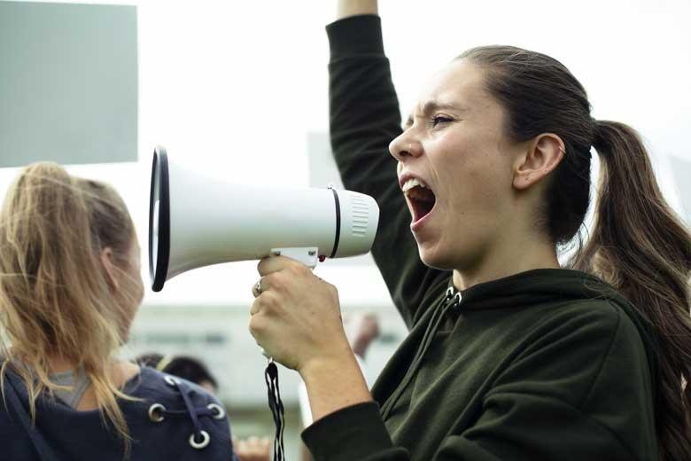 Junge Frau mit Megafon protestiert