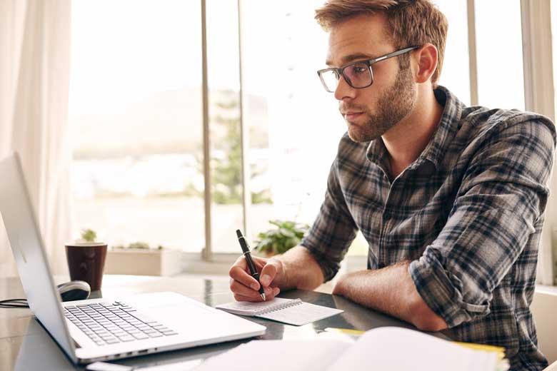 Junger Absolvent schreibt eine Bewerbung während der Corona Krise