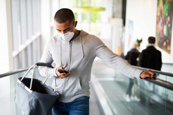 Mann kauft zur Zeit der Corona Pandemie ein er schaut auf sein Smartphone