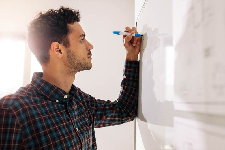Student lernt mit Hilfe eines Whiteboards