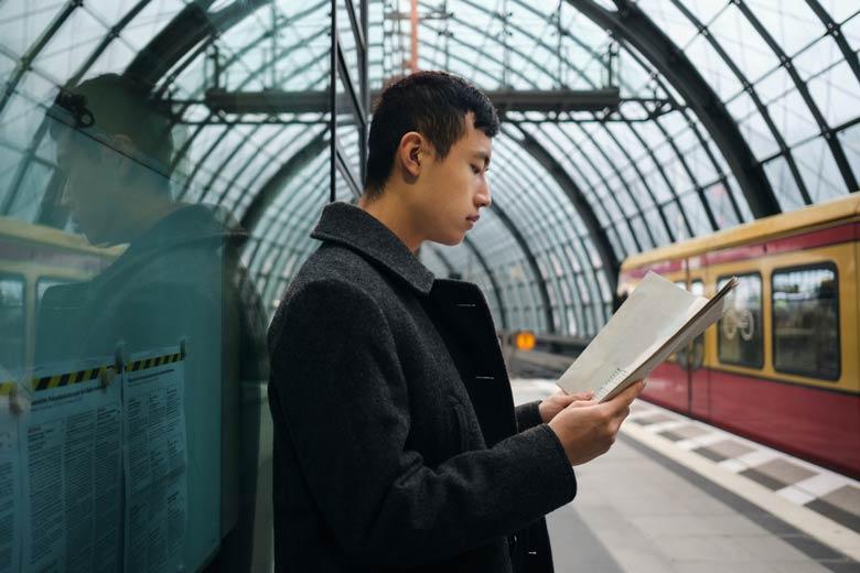 Student lernt während er auf die Bahn wartet