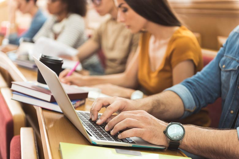 Student schreibt während der Vorlesung auf dem Laptop mit