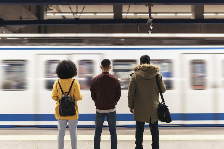 Studenten am Bahngleis warten auf einfahrende Bahn