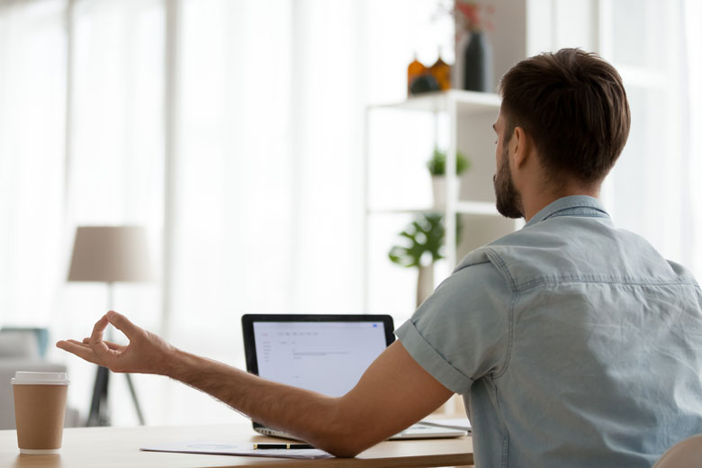 Junger Mitarbeiter meditiert an seinem Arbeitsplatz