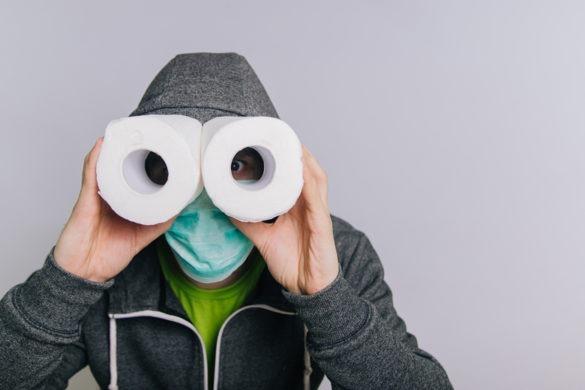 Mann mit Mundschutz schaut durch Klopapierrollen