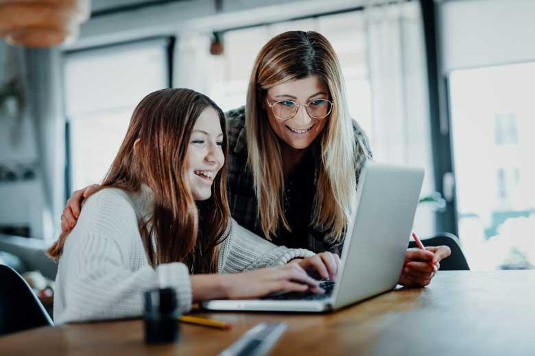 Mutter unterstützt ihre Tochter bei den Hausaufgaben