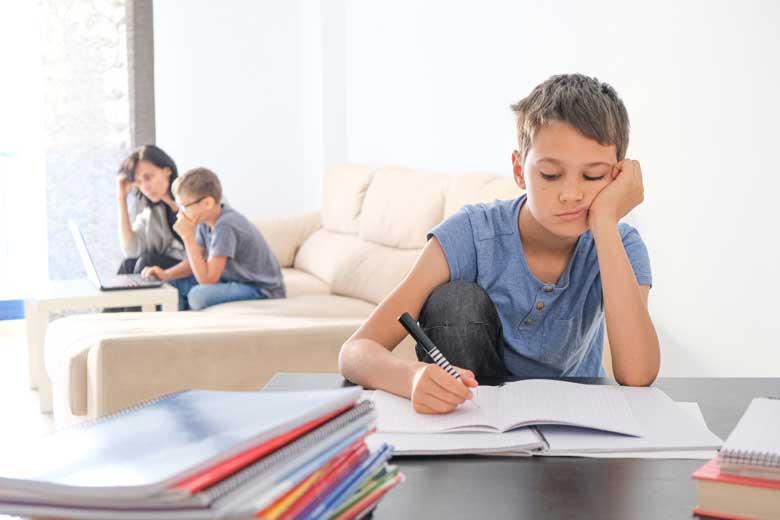 Schüler langweilt sich beim Homeschooling während sein Bruder viel Unterstützung braucht