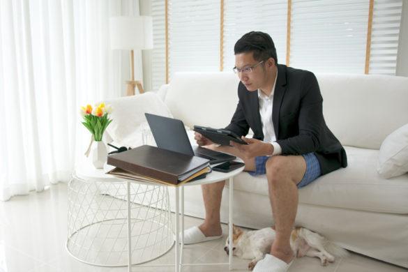 Mann sitzt in Jacket und Unterhose auf Sofa in Videokonferenz