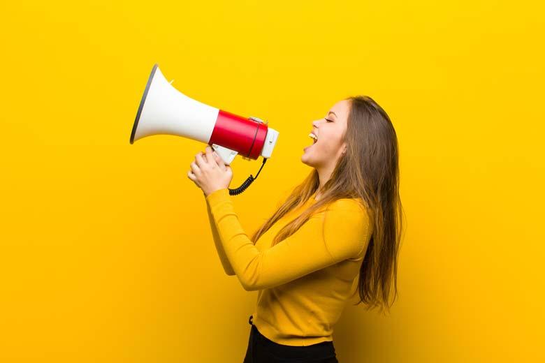Junge Frau mit Megafon: Ein Call to Action darf auf keiner Portfolio-Website fehlen