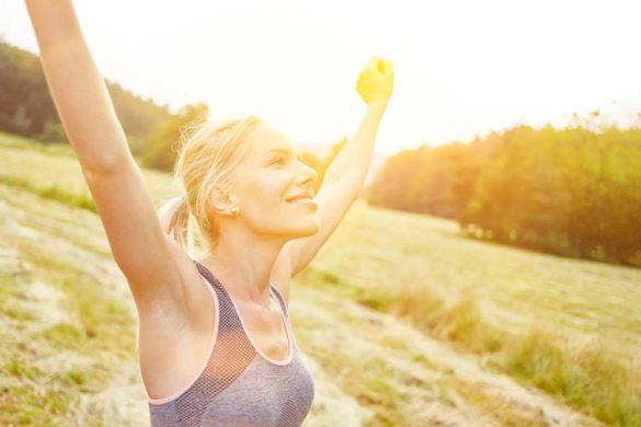 Junge Frau strotzt vor Gesundheit und streckt sich in der Natur