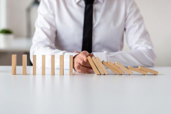 Mann sitzt an Tisch und haelt Dominosteine mit Finger an verdeutlichung change management