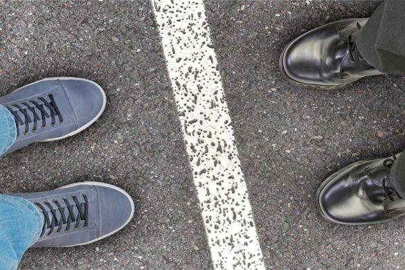 Zwei Personen stehen sich gegenüber, getrennt von einer weißen Linie