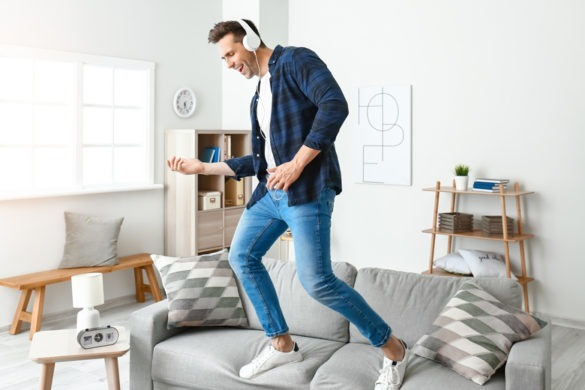 junger Mann steht auf Sofa spielt Luftgitarre