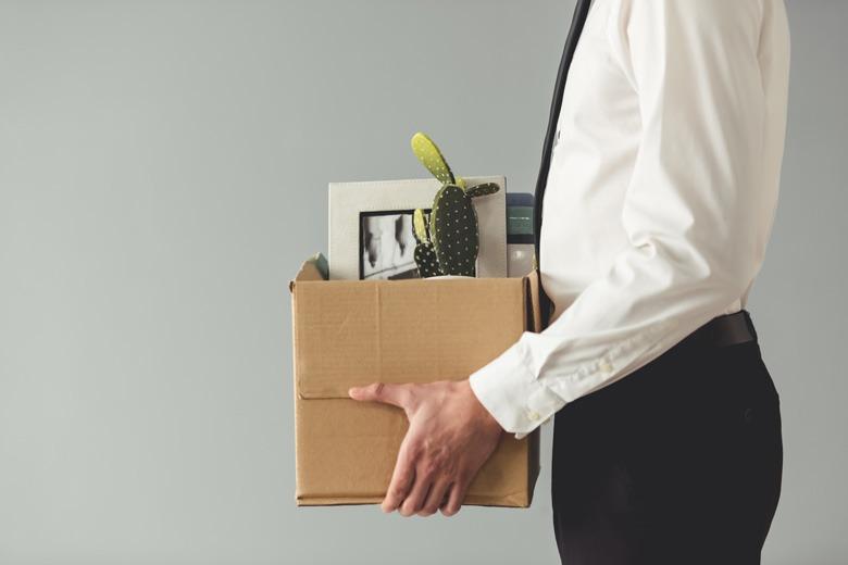 Geschäftsmann mit einer Umzugskiste verlässt seinen Arbeitsplatz