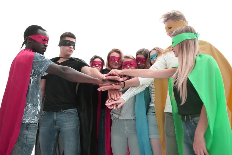 Junge Menschen als Helden verkleidet in gemeinschaftlicher Pose