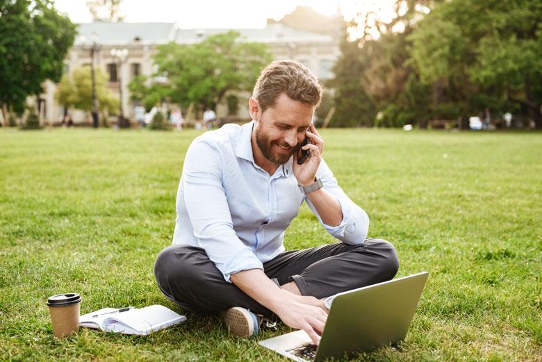 Mobiles Arbeiten: Mann mit Laptop in Park