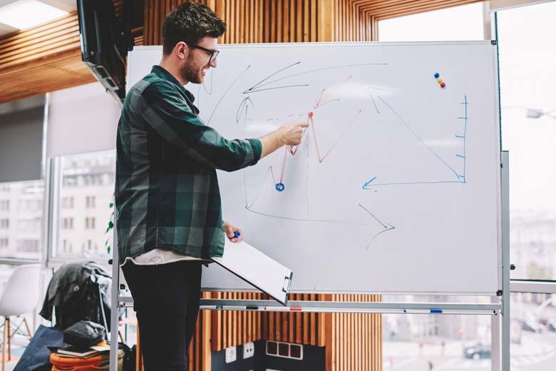 Softwareentwickler zeichnet etwas auf einer Tafel.