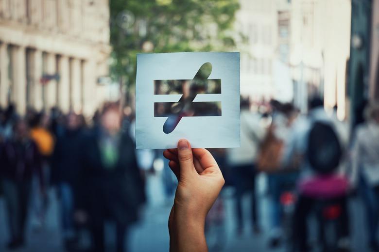 Ungleichheits-Symbol wird in die Luft gehalten